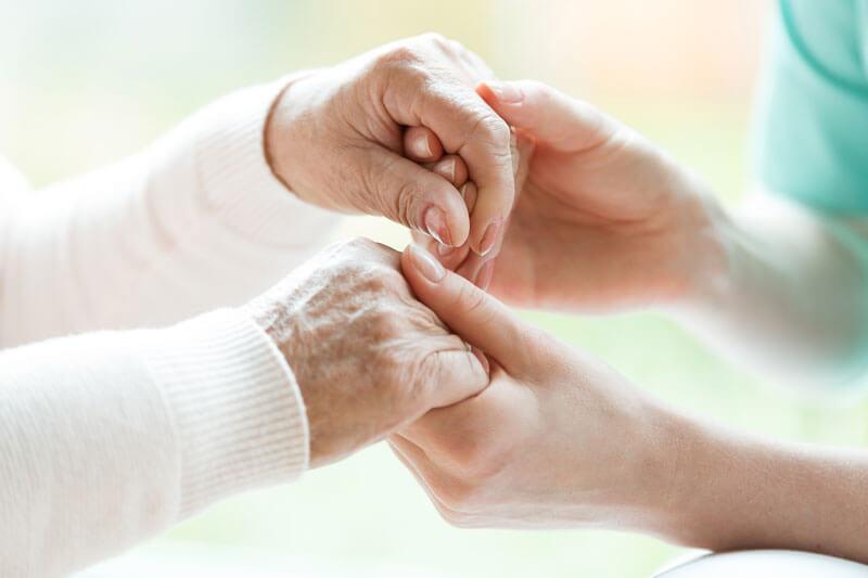 Pflegerin hällt Hände einer älteren Frau