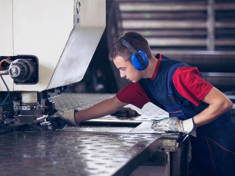 In einer Fabrik arbeitet Industriearbeiter in der Metallpresse, die ein bearbeitbares Stahlstück hält.