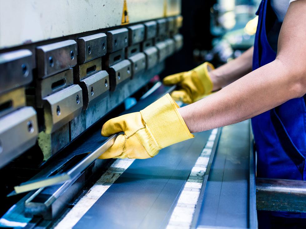 Arbeiter erstellt maschinell Bauteil aus Metall