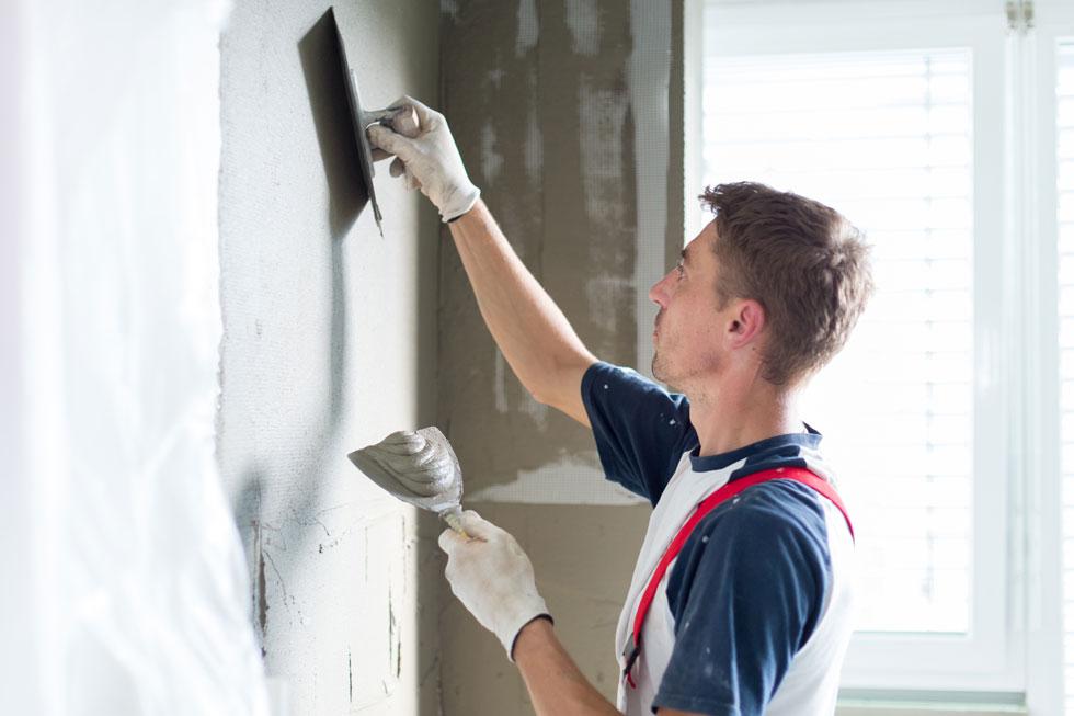 Handwerker streicht Wand mit Beschichtungsmaterial ein