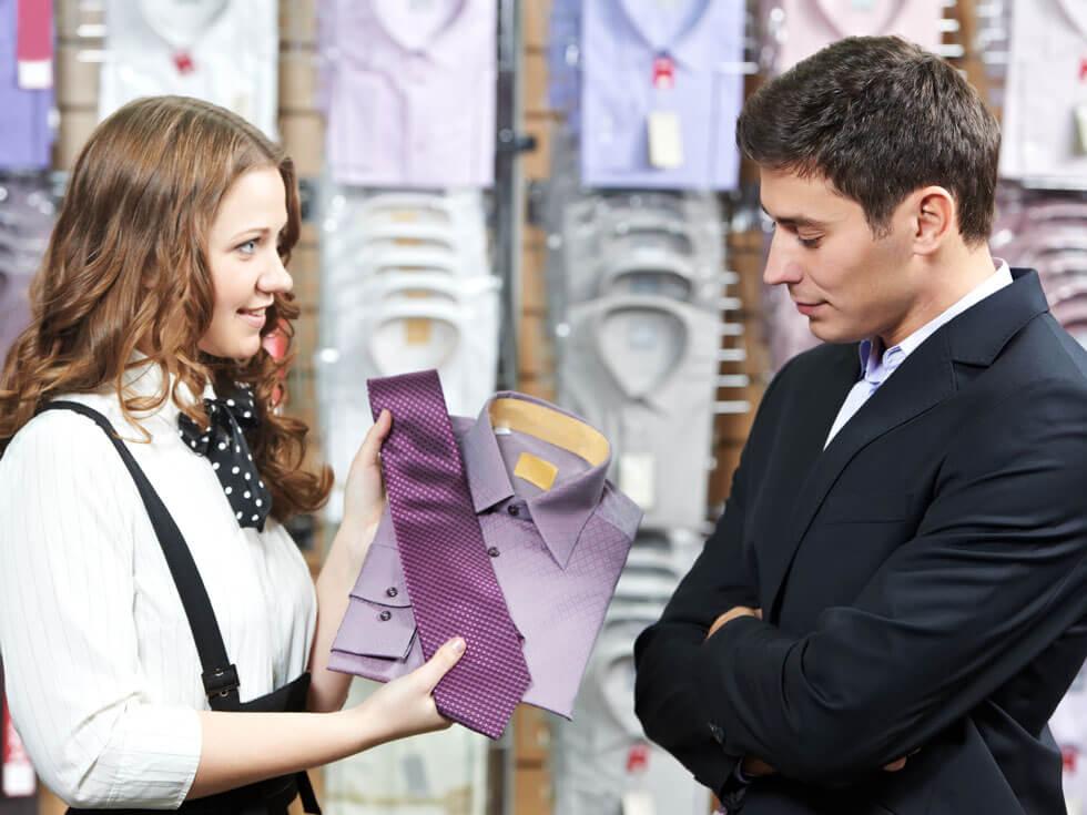 Verkäuferin berät Kunden beim Kauf einer Krawatte