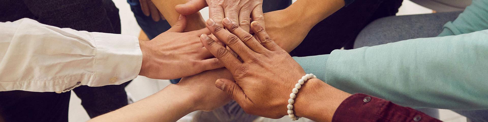 Menschen unterschiedlichen Alters und Nationalitäten legen ihre Hände übereinander und symbolisieren ihre Einheit und Unterstützung. Team von Menschen, die für produktive Arbeit und ein positives Ergebnis eingerichtet sind.