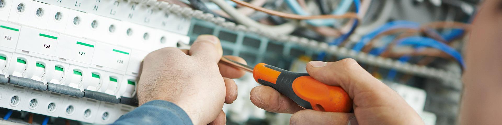 Elektriker mit Schraubenzieher beim Verengen der elektrischen Stelleinrichtung im Sicherungskasten