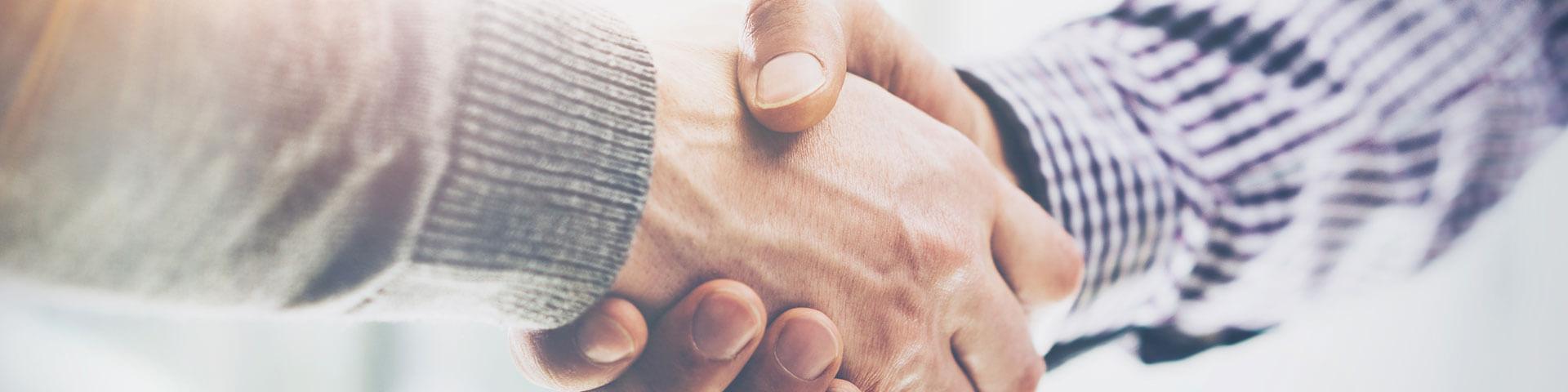 Nahaufnahme eines Handschlag zwischen 2 Menschen